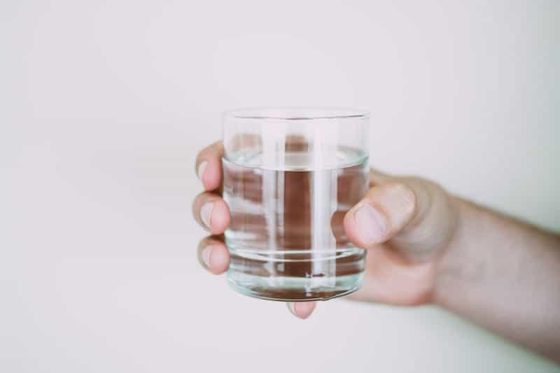 mano di uomo che stringe un bicchiere di acqua